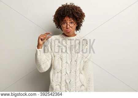 Doleful Pity Miserable Young Dark Skinned Lady Shapes Very Tiny Object, Shows Which Salary She Has,