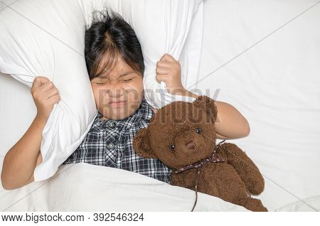 Little Girl Lying In Bed Covering Head With Pillow Because Too Loud Annoying Noise. Irritated Child