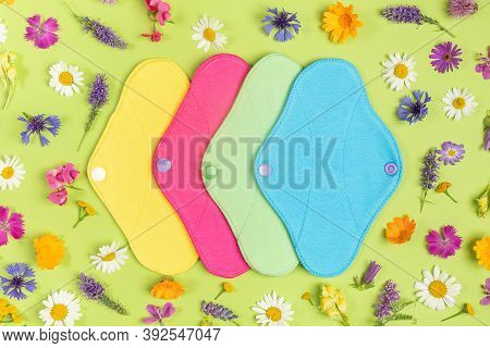 Colored Reusable Menstrual Pads On Green Background With Natural Colorful Wild Flowers. Health Care