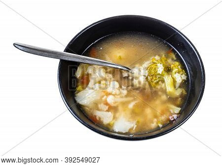 Soup With Stelline (italian Pasta) And Vegetables (cauliflower, Broccoli, Etc) In Black Bowl With Sp