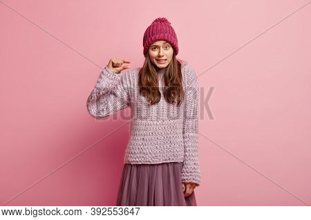 I Need Little Bit. Puzzled Lady Shows Very Tiny Object, Shapes Something Small, Wears Headgear, Knit
