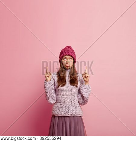 Dissatisfied Caucasian Young Woman Gazes Upwards, Purses Lower Lip With Displeasure, Discontent With