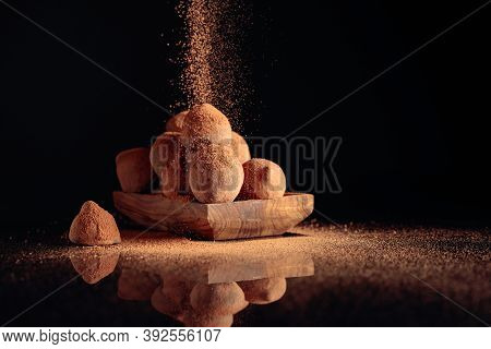 Chocolate Truffles In Small Wooden Dish Sprinkled With Cocoa Powder. Black Reflective Background. Co