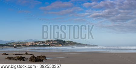 A Sandy Beach Panorama Landscape With Seaside Village In The Hills Behind