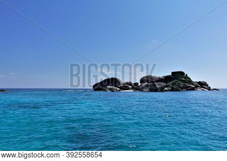 Against The Backdrop Of The Turquoise Andaman Sea And The Azure Sky, A Small Rocky Island. Large Smo