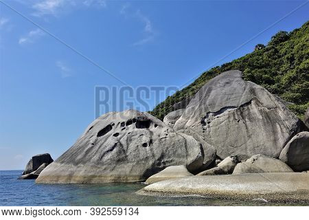 Huge Smooth Ancient Boulders Lie On The Shores Of A Green Island In The Andaman Sea. The Turquoise W