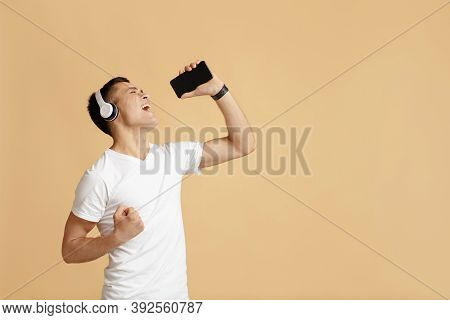Have Fun Staying At Home Alone. Young Happy Guy Enjoys Singing With Headphones And Uses Smartphone W