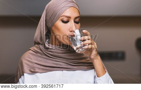 Muslim Woman Drinking Water From Glass Standing In Modern Kitchen At Home, Wearing Hijab Headscarf.
