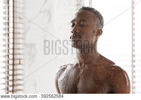 Attractive Black Guy Taking Refreshing Shower In The Morning Standing Under Falling Water In Modern