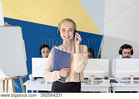 Attractive Female Hotline Operator Looking At Camera And Smiling In Modern Office. Portrait Of Helpd