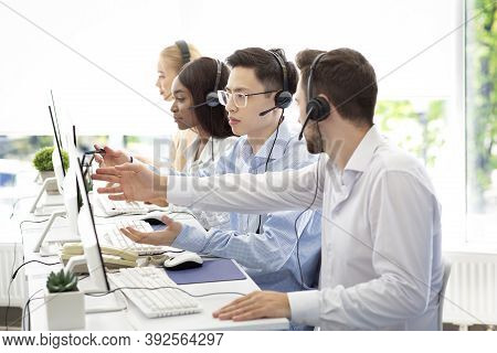Customer Support Service Concept. Helpline Operator Consulting His Colleague At Call Centre. Technic