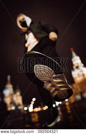 A Man In A Hood And Mask Raised His Leg To Punch Or Show Off His Soles Against The Backdrop Of Red S