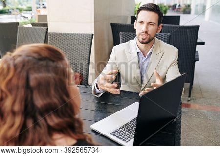 Frowning Young Entrepreneur Actively Gesturing When Talking To His Colleague At Meeting And Trying T