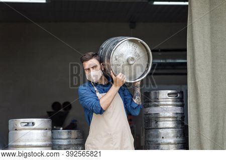 Young Man Working At Warehouse In Brewery Or Employee With Keg. Handsome Millennial Man With Tattoos