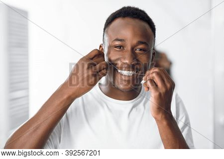 Toothcare And Hygiene. African American Guy Flossing Teeth Using Floss Smiling To Camera Standing In