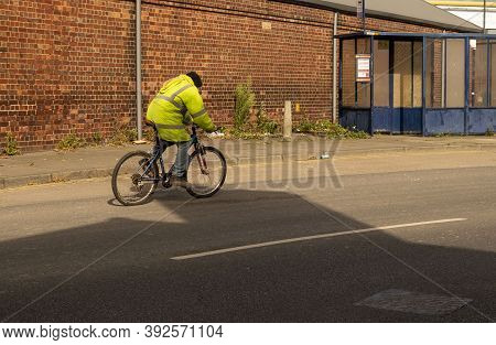Doncaster, Yorkshire, England -  October 7, 2020. Worker Riding A Bicycle With An Hi Vis Jacket  On