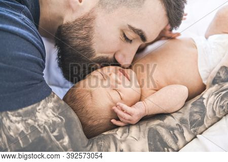 Father Lay On Bed With His Newborn Baby Daughter