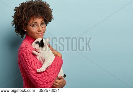 Sideways Shot Of Calm Tender Woman Holds Small Sleepy Puppy Closely To Chest, Snuggles French Bulldo
