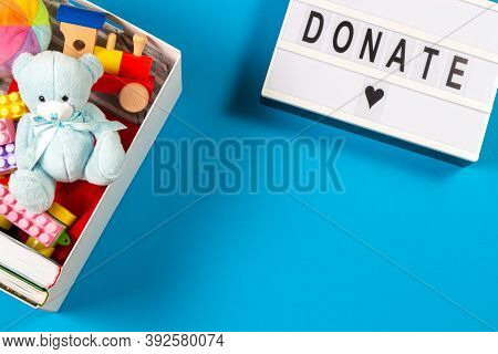Donation Concept. White Lightbox With Text Donate And Donation Box With Toys Books Clothing And On L
