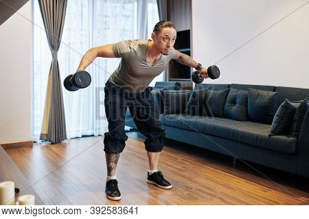 Fit Mixed-race Man Doing Dumbbell Flys When Working On His Chest, Shoulder And Triceps Muscles