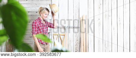 Smiling Woman In Vegetable Garden Isolated On White Wooden Shed Background With Gardening Tools, Use