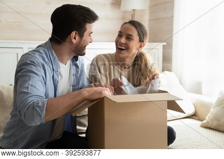 Overjoyed Laughing Millennial Husband And Wife Unboxing Packages After Relocation