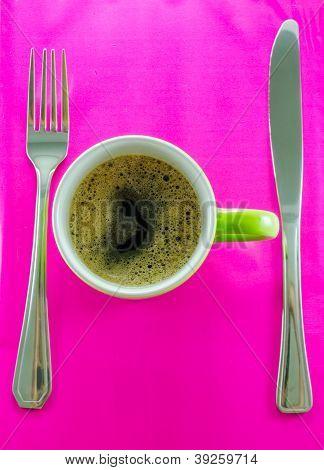 Green mug with coffee on saucer with cutlery.