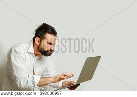 Caucasian Man Looking With Displeasure Angrily Into Laptop Monitor Isolated On Gray Background. Side