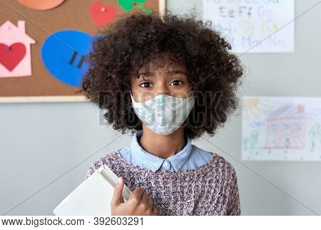 Cute Small Elementary Reopen School Pupil African American Kid Child Girl Wearing Face Mask Looking