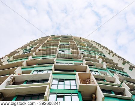 Russia, Sochi 18.02.2020.green Skyscraper In The Shape Of A Semicircle With White Ledges Against A C