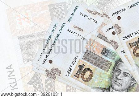 10 Croatian Kuna Bills Lies In Stack On Background Of Big Semi-transparent Banknote. Abstract Presen