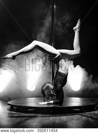 Sexy Slender Woman Dancing On A Pylon In The Interior Of A Nightclub With Light And Smoke. Pole Danc