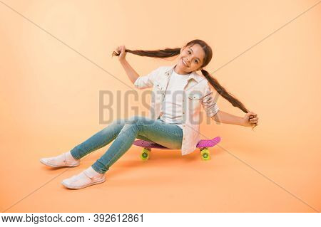 Girl Show Long Ponytail Hairstyle Sit Penny Board Yellow Background. Child Cute Hairstyle Ride Penny
