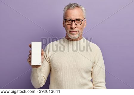 Headshot Of Mature Bearded Man Wears Glasses And White Jumper, Holds Little Box With Empty Blank Spa