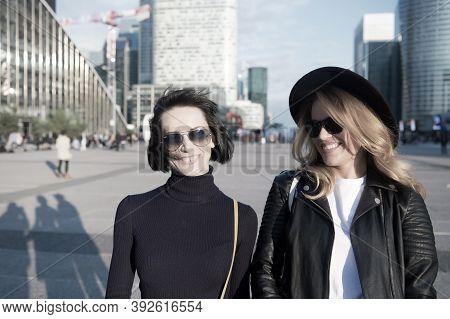 Women Smile In Fashionable Clothes In Business District Of La Defense, Paris. Happy Girls Walk On Su