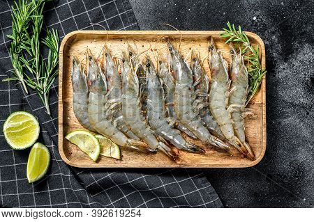 Whole Fresh Raw Langoustine Prawns, Shrimps On A Wooden Tray. Black Background. Top View