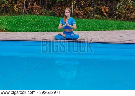 Young Woman Doing Yoga Exercises Near The Swimming Pool Ourdoors. Woman Sitting In Lotus Position.