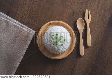 Cooked White Rice In A Wooden Dish With Green Onion Sliced On Top With Wooden Spoon, Wooden Fork And