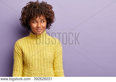 Headshot Of Curious Satisfied Dark Skinned Woman With Curly Haircut, Looks Away With Intention Or In