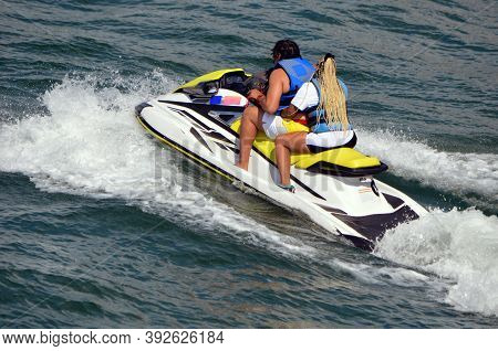 Afro American Man And Woman Riding Tandem On A Jetski
