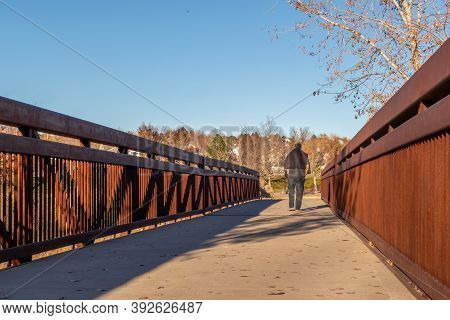 A Man Walking On The Bridge In A Small Neighborhood Park In Denver, Colorado On A Sunny October Day