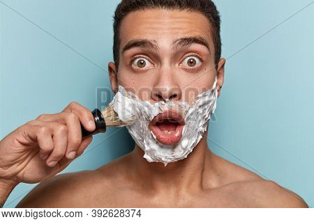 Hipster Guy With Astonished Facial Expression Applies Shaving Gel With Brush, Gazes With Stupor At M
