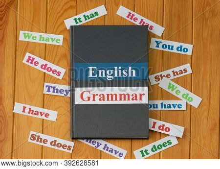 English Cards On Textbook Surrounded By English Grammar Cards On Wooden Board