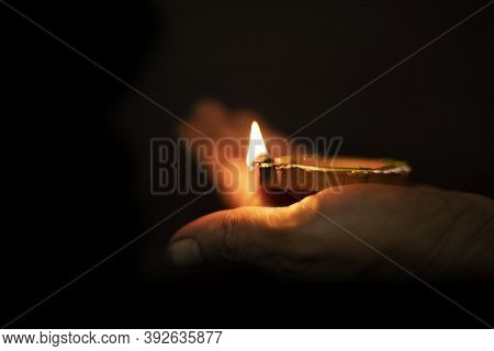 Happy Diwali - Hand Holding Diwali Clay Lamp In The Dark Background,