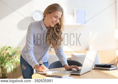 Young Business Woman Standing In Her Home Office Reading Notes.