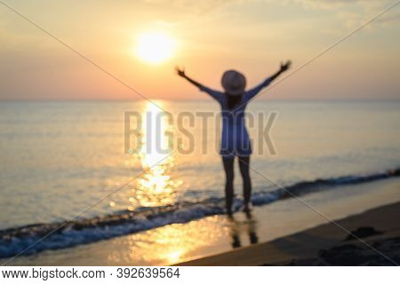 Blurred Image Of Woman On Beach In Sunset. People In Vacation. Woman On Beach In Vacation In Sunset