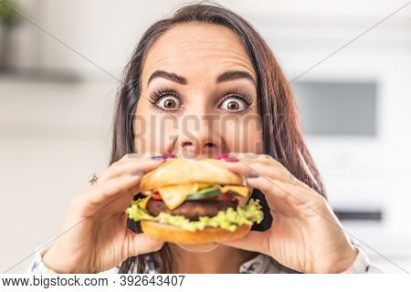 Woman With Eyes Wide Open Tries To Bite Into A Big Juicy Hamburger.
