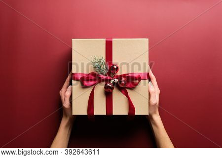 Female Hands Holding Kraft Paper Gift Box Decorated Red Ribbon, Balls, Fir Branch Over Marsala Red B