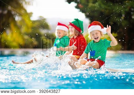 Christmas Vacation On Tropical Island. Kids In Santa Hat Playing In Swimming Pool On Family Xmas Vac