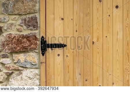 New Wooden Gate With A Black Hinge Of The Stone Building. Copy Space